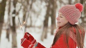 Ein glückliches junges Schulmädchen mit funkelnden Funken von Bengal-Lichtern unter dem Winterwald am Vorabend neues Jahr ` s stock footage