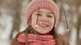 Ein glückliches junges Schulmädchen mit funkelnden Funken von Bengal-Lichtern unter der Winterwaldgesichtsnahaufnahme Am Vorabend stock video footage
