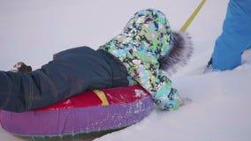 Ein glückliches Kind fährt in snowtube auf eine Schneezeitlupe Schneewinterlandschaft Draußen Sport stock footage