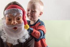 Ein glückliches Kind hält eine Santa Claus-Maske und eine leere Fahne Grußkarte mit Weihnachten Das Konzept von Weihnachtsfeierta Lizenzfreie Stockfotos