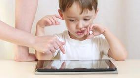Ein glückliches Kind sitzt an einem Tisch und spielt auf einer Tablette Mutter ` s Hände helfen dem Kind, auf der Tablette zu spi stock video footage
