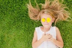 Ein glückliches kleines Mädchen, das auf dem Gras liegt Stockbild