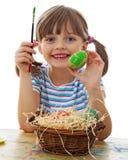 Ein glückliches kleines Mädchen, das Ostereier malt stockfotografie