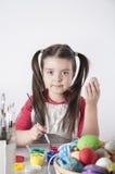 Ein glückliches kleines Mädchen, das Ostereier malt Stockfoto