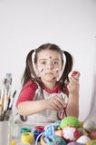 Ein glückliches kleines Mädchen, das Ostereier malt Stockbild