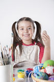Ein glückliches kleines Mädchen, das Ostereier malt Lizenzfreies Stockfoto