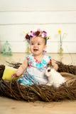 Ein glückliches kleines Mädchen in einem Kleid mit Blumen auf ihrem Kopf sitzt in einem Nest und hält einen netten flaumigen weiß lizenzfreie stockbilder