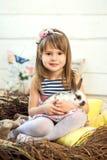 Ein glückliches kleines Mädchen in einem Kleid sitzt in einem Nest und hält einen netten flaumigen weißen Osterhasen stockbild