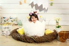 Ein glückliches kleines Mädchen mit Blumen auf ihrem Kopf sitzt in einem dekorativen Ei Osterei in der Studiolandschaft lizenzfreie stockfotografie
