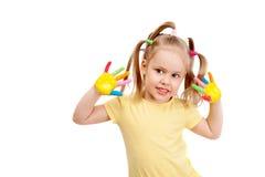 Ein glückliches kleines Mädchen mit den hell gemalten Fingern Stockfotografie
