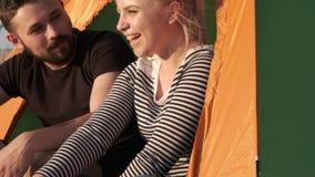 Ein glückliches liebevolles Paar sitzt in einem Zelt Ein junger Mann erzählt lustige Geschichten Eine junge Frau lacht stock video
