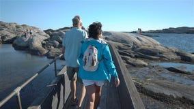Ein glückliches liebevolles reifes Paar genießt einen Weg unter den Küstensteinen auf der Küste stock video footage