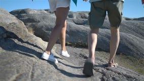 Ein glückliches liebevolles reifes Paar genießt einen Weg unter den Küstensteinen auf der Küste stock video