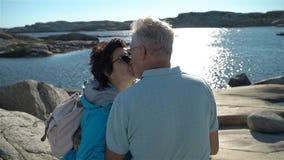Ein glückliches liebevolles reifes Paar genießt einen Weg unter den Küstensteinen auf der Küste stock footage
