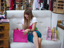 Ein glückliches Mädchen, das auf einem Sofa nahe bei ihren Einkaufstaschen auf einem Shophintergrund sitzt Ein Mädchen, das ihre  Lizenzfreie Stockbilder