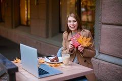 Ein glückliches Mädchen, das in einem Café sitzt, ein Geschenkbox- und Herbstgelb lächelt und hält draußen lizenzfreie stockbilder