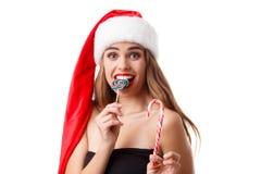Ein glückliches Mädchen in einem Sankt-Hut hält farbige Weihnachtssüßigkeiten und Bisse eine von ihnen Lokalisiert auf Weiß Stockfotografie