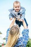 Ein glückliches mather, das ein lachendes Baby bis zum blauen Himmel hält Stockfoto