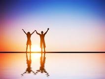 Ein glückliches Paar in der Liebe zusammen mit den Händen angehoben lizenzfreies stockbild