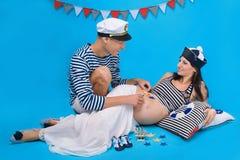 Ein glückliches Paar während der Schwangerschaft in einer Marineart Stockfotografie