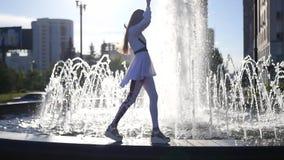 Ein glückliches schönes vorbildliches Mädchen geht entlang den Rand des Brunnens, sich freut, anhebt ihre Hände oben, hinter die  stock footage