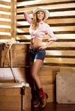 Ein glückliches und sexy Cowgirl in einer Scheune Lizenzfreies Stockfoto