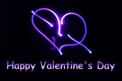 Ein glühendes Neonherz und ein Aufschrift glücklicher Valentinsgruß ` s Tag an Lizenzfreies Stockfoto