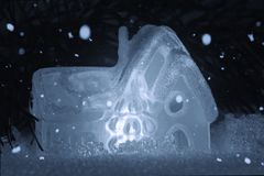 Ein glühendes Spielzeughaus steht im Schnee gegen den Hintergrund von Weihnachtsbaumasten Weihnachten, neues Jahr oder Winter stockfotografie