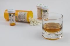 Ein Glas Alkohol und Flaschen pharmazeutische Produkte lizenzfreies stockfoto