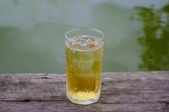 Ein Glas Bier mit Eis auf Holztisch, trinkend im heißen asiatischen Land mit kühlem alkoholfreiem Getränk Stockfotografie
