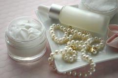 Ein Glas der Luxusschönheitsgesichtscreme und der Serumflasche mit Perlen auf rosa Farbhintergrund mit Kopienraum stockfotografie