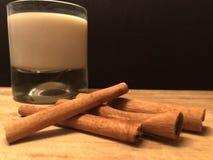 Ein Glas der Milch- und Zimtrinde auf dem hölzernen Schneidebrett mit schwarzem Hintergrund Lizenzfreies Stockfoto
