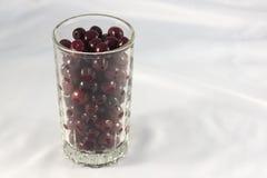 Ein Glas der reifen Kirsche auf einem weißen Hintergrund Lizenzfreie Stockfotos
