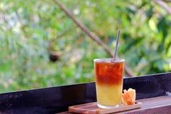 Ein Glas des alkoholfreien Getränkes des Eistees in einem hölzernen Behälter mit einer orange Blume auf hölzernem Balkon lizenzfreies stockfoto