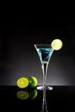 Ein Glas des blauen Cocktails mit grünem Kalk auf der Bar mit Dunkelheit zu Stockbild