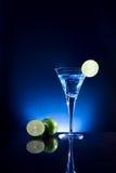 Ein Glas des blauen Cocktails mit grünem Kalk auf der Bar mit dunklem t Stockbild