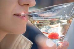 Ein Glas des Champagners oder des Martinis mit einer Kirsche auf den Lippen eines Mädchens Stockfoto