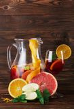 Ein Glas des Cocktails mit Erdbeeren und Minze und ein orange, Apfel und Pampelmuse auf einem hölzernen braunen Hintergrund Stockbild