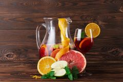 Ein Glas des Cocktails mit Erdbeeren und Minze und ein orange, Apfel und Pampelmuse auf einem hölzernen braunen Hintergrund Lizenzfreie Stockfotografie