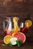 Ein Glas des Cocktails mit Erdbeeren und Minze und ein orange, Apfel und Pampelmuse auf einem hölzernen braunen Hintergrund Stockfoto
