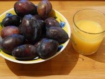 Ein Glas des Orangensaftes und der Platte mit Pflaumen lizenzfreies stockfoto