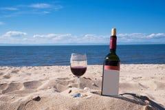 Ein Glas des Rotweins und der Flasche auf dem Strand an einem sonnigen Tag des Sommers Meer und blauer Himmel im Hintergrund Lizenzfreies Stockbild