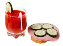 Ein Glas des Tomatesafts und des Wurstsandwiches Stockfotografie
