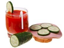 Ein Glas des Tomatesafts und des Wurstsandwiches Stockbilder