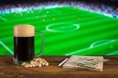 Ein Glas dunkles Bier, pistachioson mit Notizblock und Dollarscheine auf dem Hintergrund des Fußballstadions Mit Kopienraum lizenzfreie stockfotografie