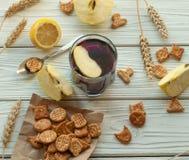 Ein Glas eines Fruchtgetränks (Saft), der Cracker, der frischen Äpfel und der Zitrone Lizenzfreies Stockfoto