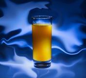 Ein Glas frischer Orangensaft auf einem abstrakten blauen Hintergrund Nahaufnahme stockbild
