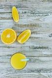 Ein Glas frischer Orangensaft und orange Fr?chte auf einem Holztisch vertikale Ansichtnahaufnahme Auffrischungszitrusfruchtgetr?n stockbilder