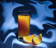 Ein Glas frischer Orangensaft und Scheiben der Orange auf einem abstracton blauen Hintergrund lizenzfreie stockbilder