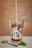 Ein Glas gefrorener Kaffee und verschüttet werden Milch stockfoto